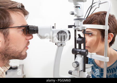 Slit Lamp eye control with the Ophthalmologist /pretty woman during an exam with Slit Lamp / the ophthalmologist in eyes clinic doing cornea and retin - Stock Photo