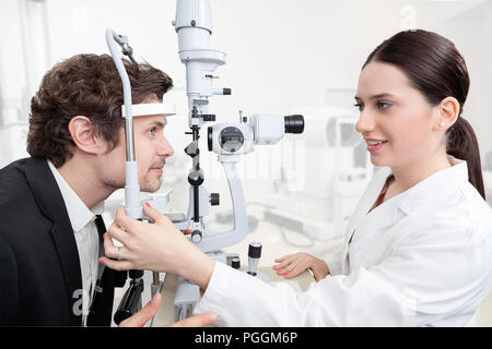 Eye Woman Doctor Adjusting Slit Lamp / handsome man during a cornea exam / the oculist in eyes clinic doing crystalline lens diagnostic / high technol - Stock Photo