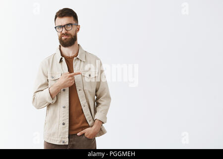 Indifferent displeased adult european male entrepreneur in beige jacket over brown t-shirt and glasses with sick long hipset beard pointing right frowning from scorn and disdain, unimpressed disliking - Stock Photo