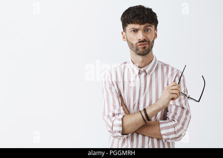 Waist-up shot of displeased picky and stylish european male entrepreneur in striped shirt taking off glasses smirking and frowning while making decision facing hard choice and thinking with doubts - Stock Photo
