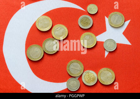 Turkish Lira bills and coins on turkish flag. The Turkish Lira is the national currency of Turkey. - Stock Photo