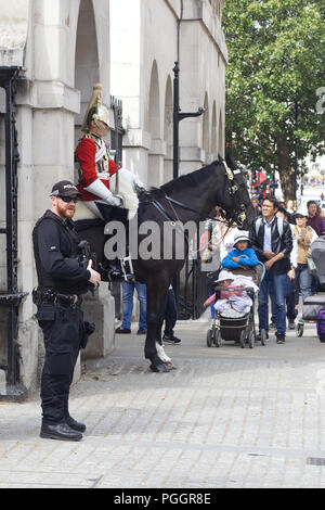 Armed police guarding the sentries at horse guards - Stock Photo