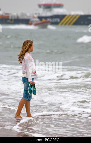 Young teenage girl stands with her bare feet in the water and looks out over the sea - Stock Photo