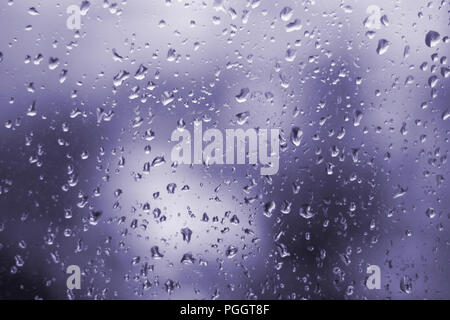 Abstract ultra violet background, texture of rain drops on glass. Raindrops on window, rainy weather. - Stock Photo