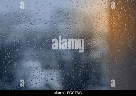 Abstract blue and yellow background, texture of rain drops on glass. Raindrops on window, rainy weather. - Stock Photo