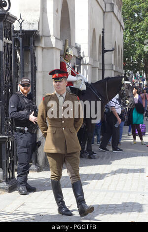 Officer inspecting the sentries at horse guards with armed police officer - Stock Photo