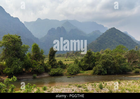 Scenic view of Nam Song River, fields and limestone mountains near Vang Vieng, Vientiane Province, Laos. - Stock Photo