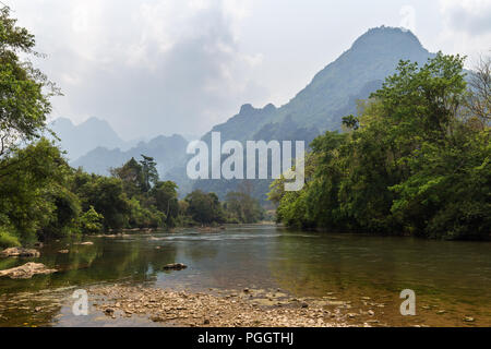 Scenic view of Nam Song River and limestone mountains near Vang Vieng, Vientiane Province, Laos. - Stock Photo