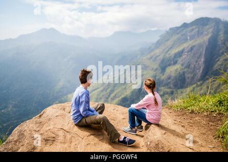 Kids enjoying breathtaking views over mountains and tea plantations from Little Adams peak in Ella Sri Lanka - Stock Photo