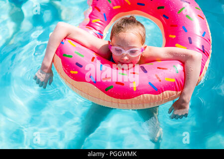 Adorable girl with pink inflatable ring swimming in a pool on summer vacation - Stock Photo