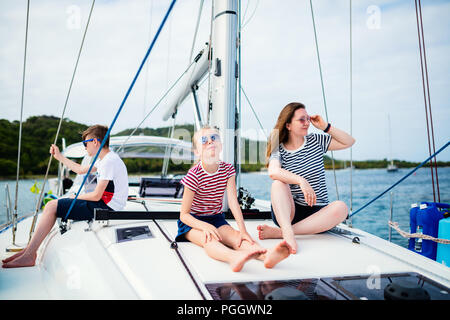 Mother and kids on board of sailing yacht having summer travel adventure - Stock Photo