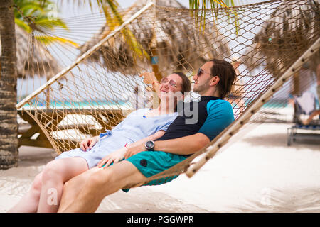 Romantic couple relaxing in hammock on tropical beach - Stock Photo