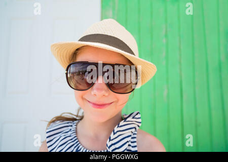 Funny portrait of little girl wearing sun glasses and straw hat outdoors on summer day - Stock Photo