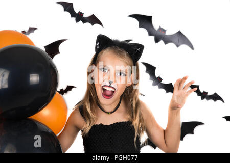 Smiley girl with black cat costume, halloween makeup and black and orange balloons at halloween party, pumpkin patch. Halloween kids. - Stock Photo