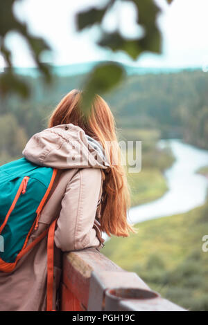 Girl traveler with red long hair standing on observation deck and looking at wild nature - Stock Photo