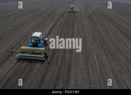 Two bright blue tractor plowing the ground against a black earth background.