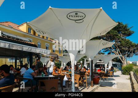 Cascais, Portugal - August 25, 2018: Tourists enjoy a drink at a patio on a restaurant at the historic Casa da Guia near Cascais on a sunny afternoon - Stock Photo