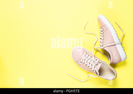 Woman fashion pink shoes on yellow background. - Stock Photo