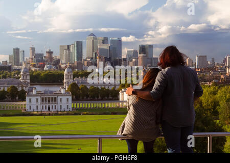 September 2017 - a couple of tourists enjoy the view of Old Royal Naval College and Canary Wharf business district in London, UK, from the viewpoint n - Stock Photo