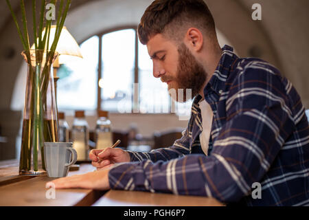 Young bearded businessman sits in cafe, home at table and writes in notebook. Man is working, studying. - Stock Photo