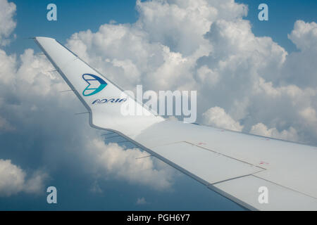 Ljubljana, Slovenia - August 25 2018: View through airplane window on wing of airplane, Adria Airways logo on wing tip, clouds and blue sky background - Stock Photo