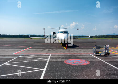 Small business, commuter jet airplane on airport, head on with apron markings on ground, copyspace - Stock Photo