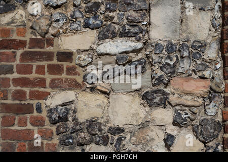 a wall of a house in Canterbury, Kent, England, partially made of ancient stones and partially from modern bricks - Stock Photo
