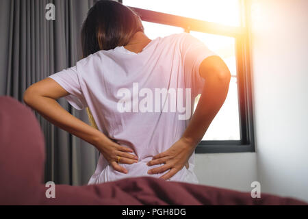 Young woman with back ache, she is sitting on the bed and touching her back - Stock Photo