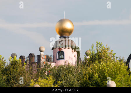 Magdeburg, Germany - August 17, 2018: View of a golden ball on the roof of the Hunderwasserhaus in Magdeburg, Germany. - Stock Photo
