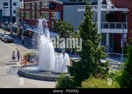 Sculpture and fountain in Olympic Sculpture park, with Space Needle in background, Seattle, USA - Stock Photo