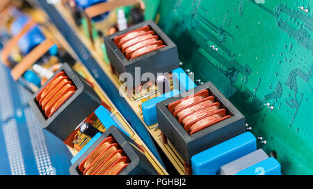 Circuit boards for PC mainboards and coils of fluorescent lamp starters. Colorful background from electronic components. Electrical engineering, eco. - Stock Photo