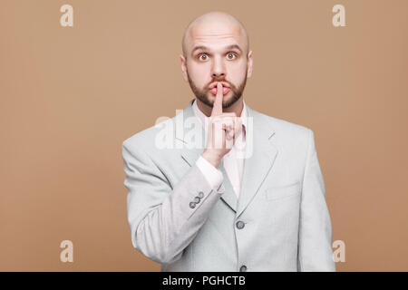 shhh this is secret. Portrait of handsome middle aged bald bearded businessman in classic light gray suit standing and looking at camera with silence  - Stock Photo