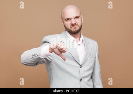its too bad. Portrait of handsome sad middle aged bald bearded businessman in classic light gray suit standing and looking at camera with thumbs down. - Stock Photo