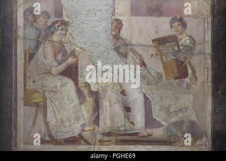 Ancient Roman musicians depicted in the Roman fresco from Herculaneum (1-79 AD), now on display in the National Archaeological Museum (Museo Archeologico Nazionale di Napoli) in Naples, Campania, Italy. Seated woman appears to be reading the musical score being played by the musicians on a tibia (Roman double flute) and a cithara (Roman lyre). - Stock Photo