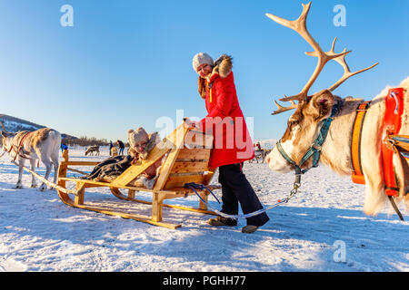 Family of mother and her daughter at reindeer safari on sunny winter day in Northern Norway - Stock Photo