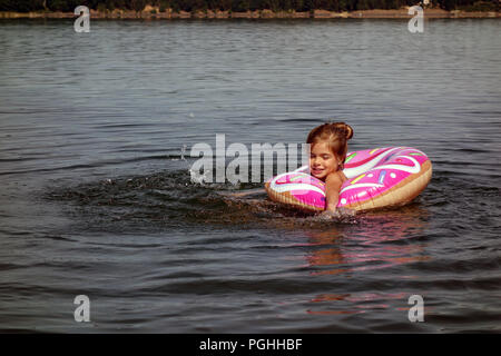 Young girl with hair in a bun having fun swimming in natural lake in inflatable pink doughnut rubber ring - Stock Photo