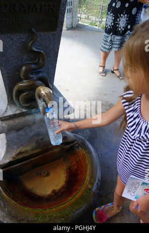 Young girl at a mineral spring fountain tap in spa town Karlovy Vary Czech Republic - Stock Photo