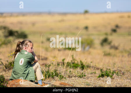 Little girl on safari vacation enjoying bush view - Stock Photo