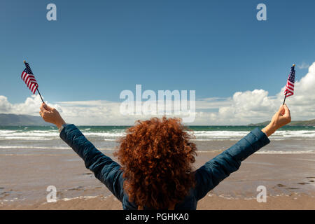 Rear view of young woman with red curly hair facing the sea while holding up American flags on a sandy beach on windy sunny day with blue skies.