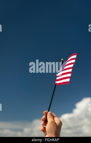 Close-up of woman's hand holding up a small American flag against blue sky. - Stock Photo