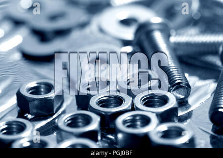 Fixings written on top of nuts and bolts in blue background - Stock Photo