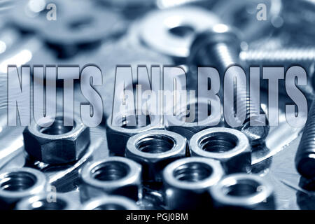 Nuts and bolts written on top of washers, nuts and bolts in blue background - Stock Photo