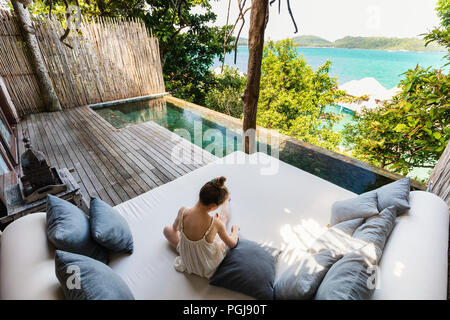 Little girl outdoors at villa with infinity swimming pool at tropical resort enjoying views over overwater bungalows - Stock Photo