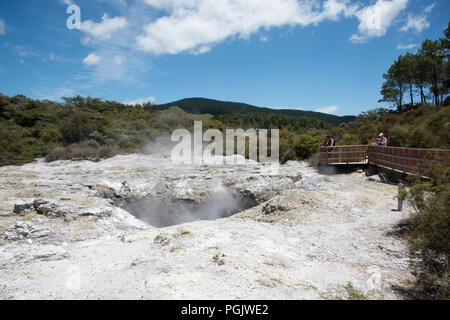 Rotorua,North Island,New Zealand-December 16,2016: Tourists viewing steaming crater at Orakei Korako geothermal area in Rotorua, New Zealand - Stock Photo