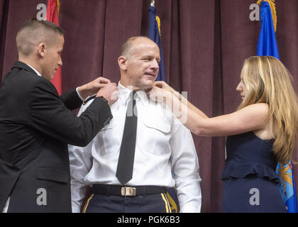 Scott Afb, IL, USA. 24th Aug, 2018. Army Lt. Gen. Stephen R. Lyons is promoted to the rank of general by Marine Corps Gen. Joe Dunford, chairman of the Joint Chiefs of Staff, his wife, son, and daughter during a ceremony at Scott Air Force Base, Aug. 24, 2018. Lyons, who was promoted to the rank of general one hour prior to the ceremony, will relieve United States Air Force Gen. Darren W. McDew, who is scheduled to retire later in the day here. Lyons is the first Army officer to lead the command. (DOD photo by Navy Petty Officer 1st Class Dominique A. Pineiro) US Joint Staff via globallook - Stock Photo