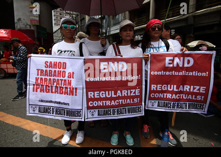 Manila, Metro Manila, Philippines. 27th Aug, 2018. Protesters holding banners during the Workers March in Manila. Thousands marched through Espana Avenue in Manila as they call for the end of contractualization and the increase of the minimum daily salary to 750 Pesos (about US$ 14). A program was held in Mendiola Bridge, near Malacanang, the presidential palace, after the march. Credit: J Gerard Seguia/SOPA Images/ZUMA Wire/Alamy Live News - Stock Photo