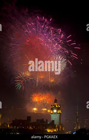 Edinburgh, Scotland, UK. 27 August 2018. Edinburgh Festival Virgin Money fireworks concert and display above castle and Princes Street Gardens to mark the end of the 2018 event. Photographed from Calton Hill with Clock tower in foreground. - Stock Photo