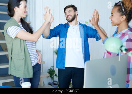 Portrait of three contemporary young people celebrating success and smiling cheerfully doing high five in modern office - Stock Photo