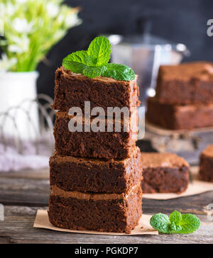 stack of square pieces of baked brown brownie pie on a gray board, close up - Stock Photo