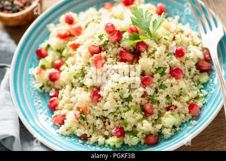 Tabbouleh salad with pomegranate seeds on turquoise plate. Closeup view. Healthy vegetarian arabic salad - Stock Photo